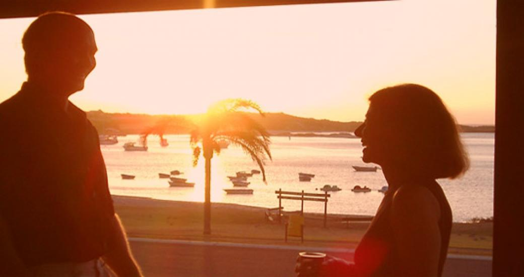 A couple watch the sunset from their veranda at Kalbarri Seafront Villas, in Kalbarri, Western Australia