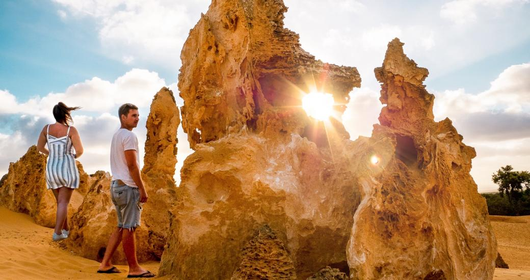 A couple marvel at the mystical Pinnacles Desert of Nambung National Park near Cervantes, Western Australia