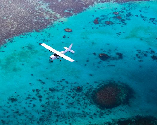 A light aircraft flies above the turquoise waters of Ningaloo Reef, Western Australia