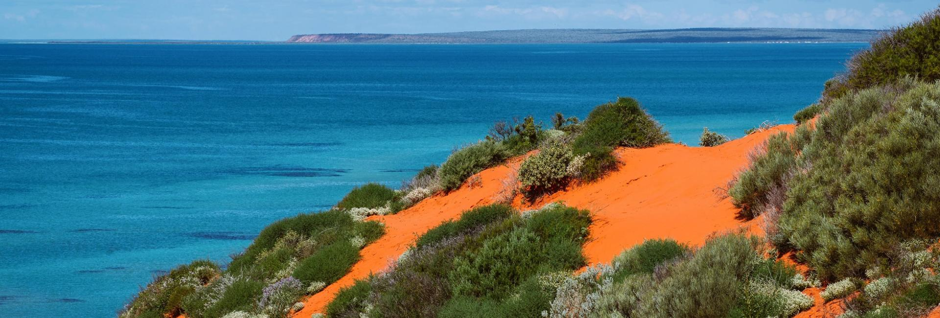 The red earth of Francois Peron National Park contrasts with the blue ocean. Shark Bay World Heritage Area, Western Australia