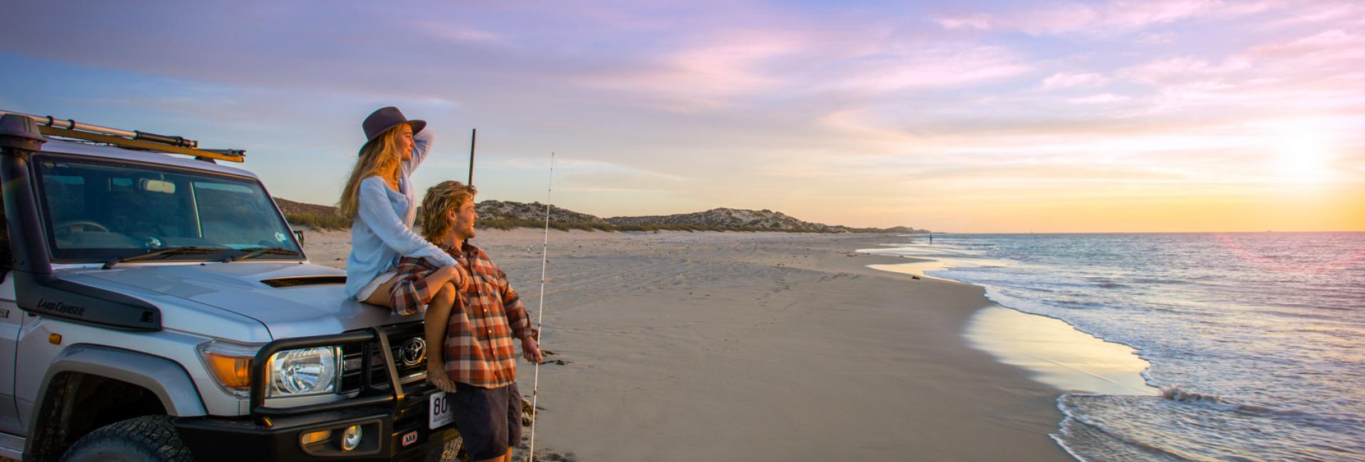 A couple lean against their 4WD after fishing from the beach in Coral Bay, Western Australia