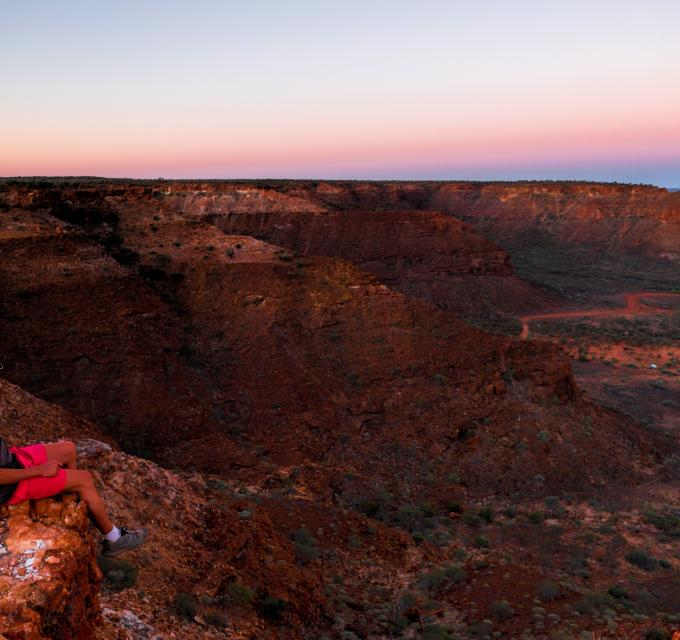 A man sits atop the range in Kennedy Range National Park, inland from Carnarvon, Western Australia