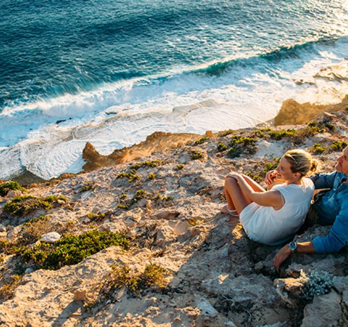 A couple sit near the edge of the Zuytdorp Cliffs at sunset, Western Australia